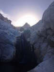 """Looking up the waterfall to see the outline of the nearby peak in sunlight.  Peak is named """"The White Throne""""."""